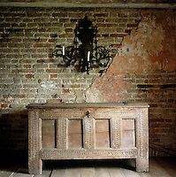 A large wrought-iron sconce hangs on an exposed brick wall above a wooden William and Mary chest