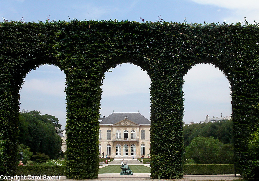 Garden view of the Rodin Museum, Paris, France, through arches of ivy.