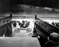 Landing on the coast of France under heavy Nazi machine gun fire are these American soldiers, shown just as they left the ramp of a Coast Guard landing boat, June 6, 1944.  CPhoM. Robert F. Sargent. (Coast Guard)<br /> NARA FILE #:  026-G-2343<br /> WAR &amp; CONFLICT BOOK #:  1041