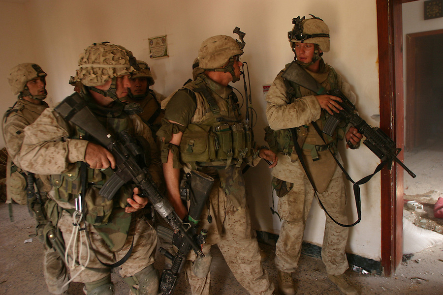 Cpl. Robert Mitchell (c.) confers with a platoon mate before he and 1st Sgt. Brad Kasal (near left) and PFC Alex Nicoll push forward into the home known as the Hell House by Kilo Co. 3rd BN 1st Marines on Nov. 13, 2004 during the Nov. 2004 assault on Fallujah. All three Marines were subsequently wounded in the house  with both Kasal and Mitchell being awarded the Navy Cross for the actions and PFC Nicoll ending part of his leg left to gunshot wounds.