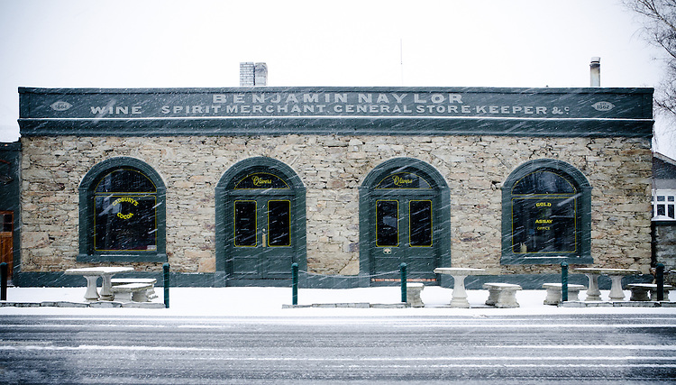 Snow falling in front of old stone buildings in winter, Clyde, Central Otago, New Zealand