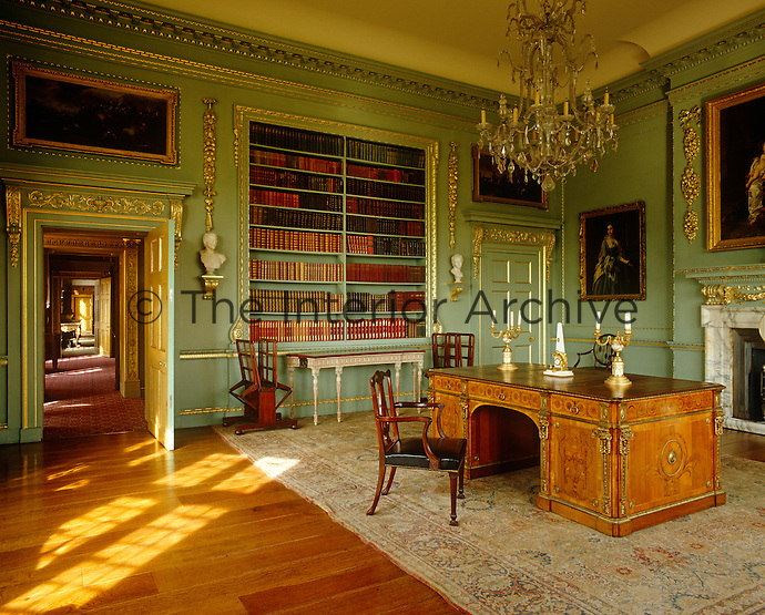 The walls of this library are painted a pale turquoise with gilded cornices and oramentation
