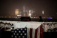 The lower Manhattan and the World Trade Center are seen while an USA flag is covered with snow in Exchange Place in New Jersey, 01/17/2016 Photo by VIEWpress