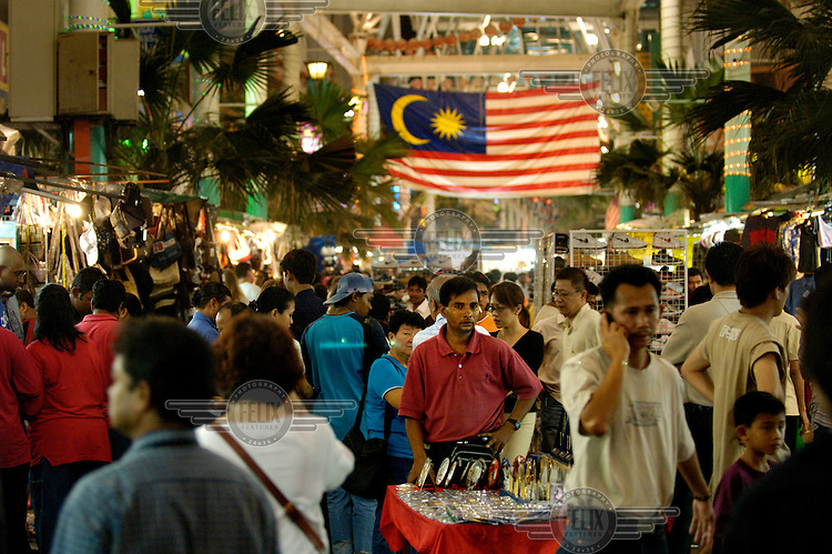 Jalan Petaling Chinatown market. Man with souvenir stall and Malaysian flag flying over the crowds in the market, which is mostly dedicated to illegal counterfeit (pirated) goods.