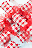 A pile of red and white gingham napkins tied with red ribbon