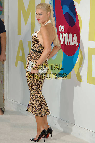 GWEN STEFANI.MTV Video Music Awards.Arrivals held at the American Airlines Arena,.Miami, 28th August 2005.full length leopard print dress white halter neck straps silver clutch bag over shoulder.Ref: ADM/JW.www.capitalpictures.com.sales@capitalpictures.com.© Capital Pictures.v-neck plunging neckline