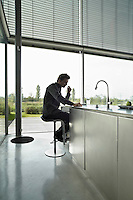 A man sits at a stainless steel breakfast bar unit in a modern kitchen.