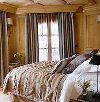 The wood-lined master bedroom has a bed cover of cashmere and fur and is decorated with fabric by Nobilis