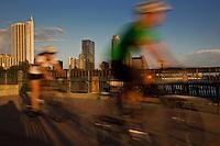 Bicyclists peddle across the Lamar Street Pedestrian Bridge overlooking the Austin Skyline