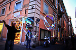 ITALY, ROME, November 3, 2011..A Resident plays with bubbles in a street in central Rome November 3, 2011. VIEWpress /Eduardo Munoz Alvarez..Italy's P.M. Berlusconi resigned on Saturday after new budget law is approved in parliament. The approval of the package will mark the final of the Berlusconi government..Local Media Report