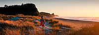 Young woman watching sunset on Three Mile beach near Okarito, West Coast, Westland Tai Poutini National Park, UNESCO World Heritage Area, New Zealand, NZ