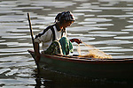 A local Nepalese woman pulls in her fishing nets from her wooden boat, at sunset on Fewa Lake, or Phewa Tal, in Pokhara, Nepal.