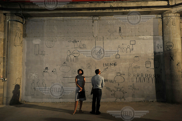 Visitors next to a wall drawing or mural at an ArtFocus exhibition in Jerusalem.