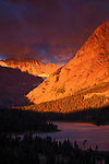 Sky Ablaze, Grinnell Point, Glacier National Park, Montana.  The glacially carved spire of Grinnell Point, illuminated by warm morning light, thrusts from the wind-whipped waters of Swiftcurrent Lake.  All the mountains, lakes, cirques and valleys show the powerful effects of the ice sheet that once covered the region.