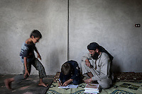 In this Sunday, Sep. 29, 2013 photo, AHMED ABU ABDU helps his son ABDU EL KADER to carry out his home task at their family house in Madaya village after attended classes in the public school in the Idlib province countryside of Syria. Children have come back to school in the rebel controlled territory despite the constant threaten of shelling and the ongoing fighting, and public schools still operating financially under the Syrian government administration. (AP Photo)