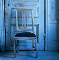 Detail of a wooden chair in front of a distressed wooden door