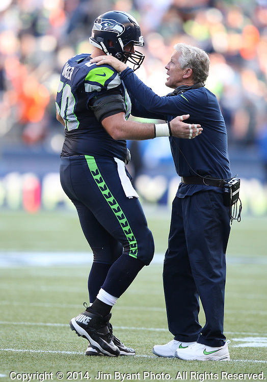 Seattle Seahawks head coach Pete Carroll talks with his All-Pro center Max Unger (60) during the game against the  Denver Broncos at CenturyLink Field in Seattle, Washington on September 21, 2014. The Seahawks won 26-20 in overtime.    ©2014. Jim Bryant Photo. All rights Reserved.
