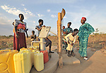 Women and girls pump water from a well constructed by the United Methodist Committee on Relief (UMCOR) in the Southern Sudanese town of Yei.