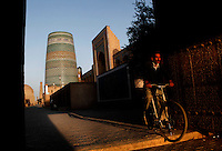 View from the front of a man cycling towards the Ata-Davarza gate, Khiva, Uzbekistan, pictured on July 7, 2010, in the late afternoon light of a summer day. The Muhammad Aminkhan Madrasah and Kalta Minar are visible in the distance.