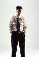 Caucasian looking man wearing a white shirt and tie looking at camera with his hands in his pant pockets