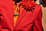 A man in the New York City Easter Parade wearing a bright orange suit and tie with a gold pin of a rabbits holding on to a carrot