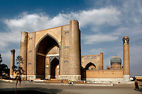 Low angle view of the Bibi-Khanym Mosque (Juma mosque), Registan square, early 15th century, Samarkand, Uzbekistan, seen at sunrise on July 16, 2010, showing the huge entrance gateway. Named after the wife of Amir Timur, 14th century ruler, the mosque was constructed following his 1399 Indian campaign. It collapsed after an earthquake in 1897 and was restored in the late 20th century. Samarkand, a city on the Silk Road, founded as Afrosiab in the 7th century BC, is a meeting point for the world's cultures. Its most important development was in the Timurid period, 14th to 15th centuries.
