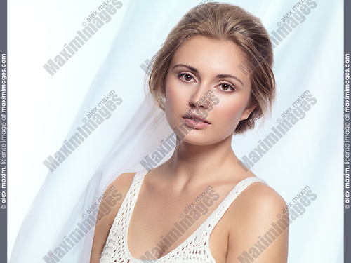 Portrait of a beautiful young woman on light blue flowy fabric background