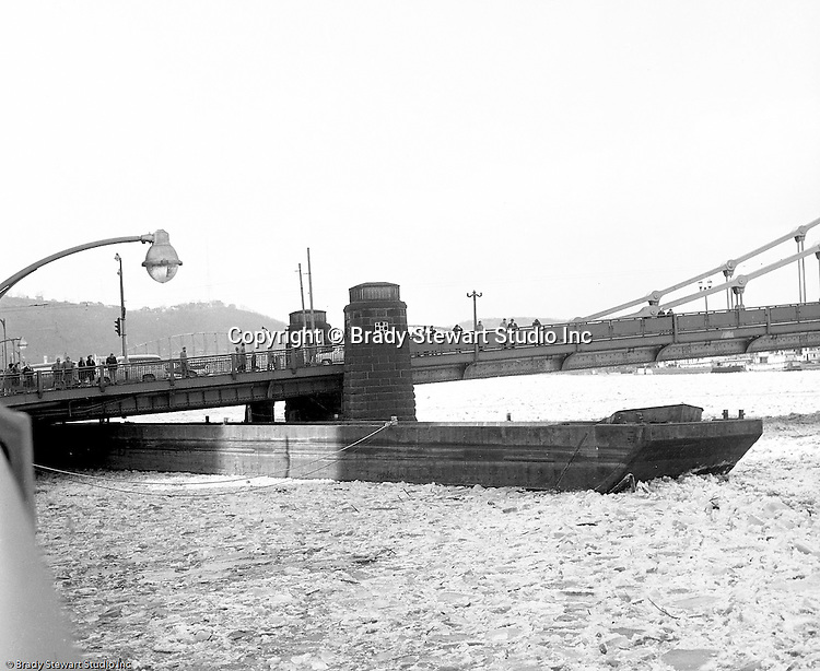 Pittsburgh PA:  High waters on the Allegheny River after a snow melt - 1959.  View of a barge stuck under the 6th Street Bridge.