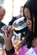 Closeup image of an industry professional smelling a glass of wine at a tasting event.