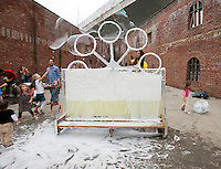 "Visitors to the 15th Annual Art Under the Bridge Dumbo Arts Festival on Saturday, September 24, 2011 enjoy the installation, ""Oil and Water"".  Created by artists, Eric Ayotte, Et.Per.Se. and Richard Oliver Wilson,  the giant bubble making device delighted children and adults during its installation.   (© Richard B. Levine)"