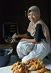 Nizria Ulva Sarwini bakes pastries in her home in Banda Aceh, on Indonesia's Sumatra Island. Her family lost their house and belongings in the 2004 tsunami. The government provided them with a new house. Church World Service, a member of the ACT Alliance, loaned her mother and other women in the neighborhood the money they needed to purchase new equipment and ingredients to restart their businesses. The women repaid their loans to a revolving fund that they jointly manage. Nizria's mother has used the profits from her pastry business to keep her four children in school. Nizria recently graduated from a local university with a degree in economics, but while she's looking for employment she assists her mother with the pastry making.