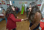 """Spearans Yoqresh Marogil (left) and Ashorena Warda Youkhana model how to shake hands when greeting other people in a church-sponsored """"child-friendly space"""" in the village of Bakhtme, Iraq, which was flooded with displaced families when the Islamic State group took over nearby portions of the Nineveh Plains in 2014. The space is sponsored by the Christian Aid Program Nohadra - Iraq (CAPNI). It includes some children from the host community as well."""