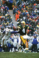 Green Bay Packers Quarterback Brett Favre dumps a shuttle pass as he's pressured by the Minnesota Vikings' John Randle during the December 22, 1996 contest. Favre threw three touchdown passes as the Packers downed the Vikings 38-10.