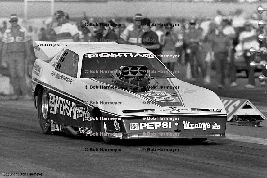 """POMONA, CALIFORNIA: Don """"The Snake"""" Prudhomme drives his Pontiac Funny Car during a 1985 NHRA drag race at Pomona, California."""
