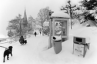 Switzerland. Canton Bern. Wengen. People walk in the snow. Swisscom public phone booth. Dustbin and trash. Dog on Leash. Father and child on sledge. Wengen is a mountain village in the Bernese Oberland of central Switzerland. Located in the canton of Bern at an elevation of 1,274 m (4,180 ft) above sea level, it is part of the Jungfrauregion and has approximately 1,300 year-round residents. 14.01.17 © 2017 Didier Ruef