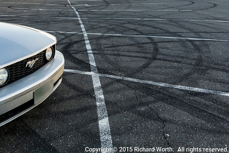 A Mustang GT in a parking lot surrounded by suggestive tire tracks.