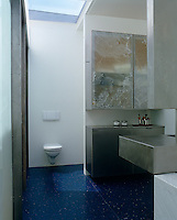 The cupboards in the bathroom  are faced in thin laminate marble in muted shades of grey and ochre constrasting with the deep blue of the terrazzo floor