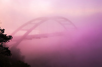 Early morning fog paints the 360 Bridge during morning sunrise on a cold winter's morning on Lake Austin, Texas.