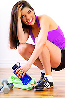 Beautiful brunette sitting with water bottle after her physical fitness workout.