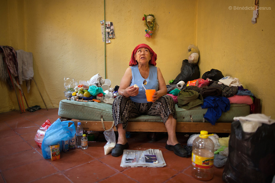 Amalia, a resident of Casa Xochiquetzal, in her bedroom at the shelter in Mexico City, Mexico on may 28, 2012. Amalia, 66, is from Michoacán and came to Casa Xochiquetzal when it first opened its doors. She wears a wig and pads her bra. She is very animated; words and songs come easily to her. She has also suffered from schizophrenia for 22 years, but despite hearing voices, she works hard not to lose touch with reality. As a way of earning a little money, she gathers plastic bottles to recycle and also helps to sell clothes in a stand operated by her boyfriend of 31 years. Casa Xochiquetzal is a shelter for elderly sex workers in Mexico City. It gives the women refuge, food, health services, a space to learn about their human rights and courses to help them rediscover their self-confidence and deal with traumatic aspects of their lives. Casa Xochiquetzal provides a space to age with dignity for a group of vulnerable women who are often invisible to society at large. It is the only such shelter existing in Latin America. Photo by Bénédicte Desrus
