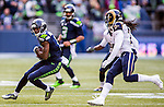 Seattle Seahawks wide receiver Paul Richardson (10) tries to run away from St. Louis Rams  cornerback James Jenkins (21) after catching a short pass at CenturyLink Field in Seattle, Washington on December 28, 2014.  The Seahawks officially wrapped up the No. 1 seed in the NFC playoffs shortly after beating the Rams, 20-6. Despite the Cowboys and Packers also winning to finish 12-4, the Seahawks (12-4) won the multi-team tiebreaker and earned home-field advantage throughout the playoffs for the second consecutive season.  ©2014. Jim Bryant Photo. All Rights Reserved.