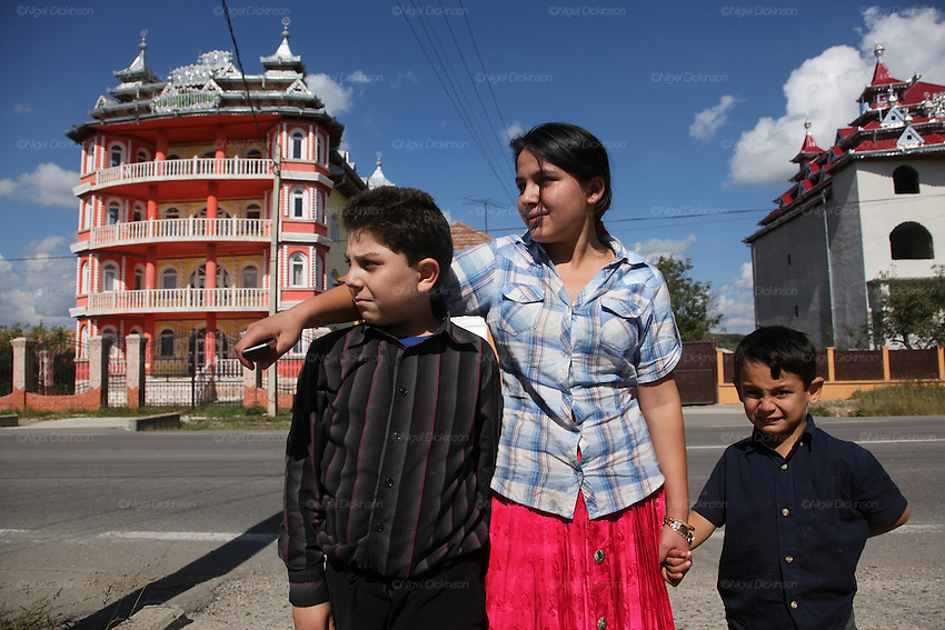 An older sister with her two brothers. Wealthy Roma Gypsy homes. Extravagant houses in garish colours, in typical Romanian Gypsy style with ornate metal zinc roofs and several balconies, often with symbols such as Mercedes Benz emblems, which was once considered the best made car. These houses or palaces often take years to build, their occupants working abroad, finishing the structures little by little. Huedin, near Cluj-Napoca, Romania