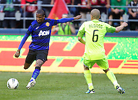 Manchester United forward Ashley Young passes the ball in front of Seattle Sounders FC midfielder Osvaldo Alonso during play at CenturyLink Field in Seattle Wednesday July 20, 2011. Manchester United won the match 7-0.