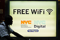 "A man passes next to a poster of free WiFi in New York, July 15, 2012. New York CIty recently unveiled plans to turn outdated public payphone infrastructure into free WiFi hotspots, according to Mashable. New Yorkers and visitors alike will be able to connect to ""NYC-PUBLIC-WIFI"" using smartphones, tablets, or laptops. local media reported. Photo by Eduardo Munoz Alvarez / VIEW."