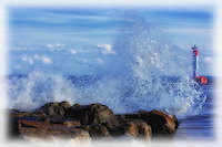 Watching the waves crash into the rocks at the base of the Oakville lighthouse pier in a photo art style.