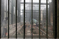 New Caledonia Glasshouse (formerly The Mexican Hothouse), 1830s, Charles Rohault de Fleury, Jardin des Plantes, Museum National d'Histoire Naturelle, Paris, France.  Low angle view, through the glass walls, showing the renovation works within. The New Caledonia Glasshouse, or Hothouse, was the first French glass and iron building.