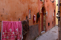 """Clothes hanging on string in front of old houses in a narrow street, Portuguese Fortified city of Mazagan, El Jadida, Morocco. El Jadida, previously known as Mazagan (Portuguese: Mazag""""o), was seized in 1502 by the Portuguese, and they controlled this city until 1769. Picture by Manuel Cohen"""