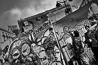 Young Spaniards paint a political graffiti on a wooden board in the protest camp on Puerta del Sol square, Madrid, Spain, 7 June 2011.