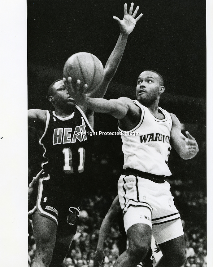 Golden State Warriors Tim Hardaway drives past Miami's Sherman Douglas. (photo/Ron Riesterer)