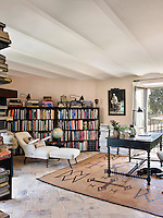 A large book collection is stored in contemporary black book shelves in the first floor study